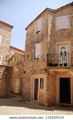 A mediterranean stone  houses with window shutters and medieval paving street(Budva, Montenegro).