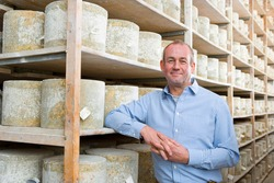 A medium shot of a owner standing in a cellar and smiling with aged cheddar cheese wheels in background.