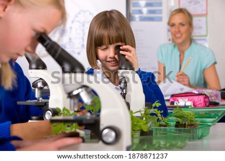 A medium shot of a Smiling girl in school uniform under selective focus looking into the microscope in a laboratory with other students in the foreground and her teacher working in the background Stock photo ©