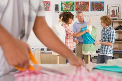 A medium shot of a teacher talking to his students about clothing in a home economics classroom with a hand cutting fabric in foreground.