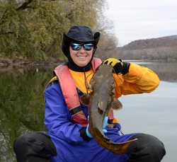 A medium sized brown olive colored flathead catfish fish being held vertically by a smiling woman in a dry suit in autumn