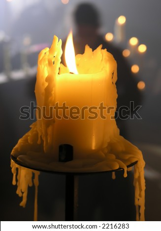 A melting candle with a worshipper