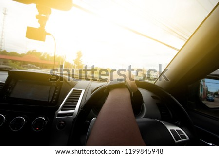 A men driving inside of car steering wheel curved in the city. #1199845948
