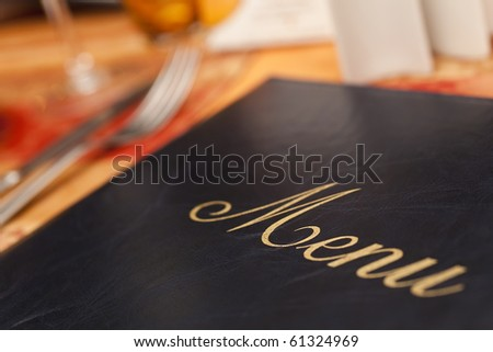 A menu and knife and fork cutlery laid on a restaurant table - stock photo
