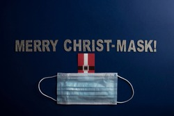 A merry christmas frase with the word play Chris mask, because of the coronavirus and use of mask to avoid the virus. A mask and a Santa tag behind the mask complement the message.