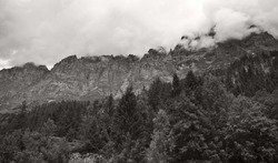 A mesmerizing grayscale shot of the beautiful rocky mountains under a cloudy sky