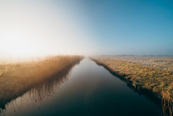 a mesmerizing shot of a reflecting river in a foggy field in Middelburg, Zeeland, The Netherlands