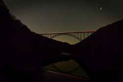 A mesmerizing view of the New River Gorge Bridge at night with traffic lights under a starry sky