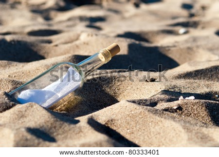 a message in a bottle lies in the sand on the beach