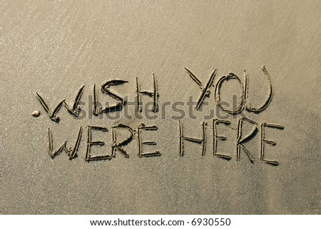 A message inscribed in the wet sand along a beach shoreline wishing you were here.