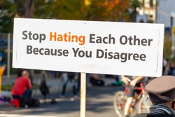 A message written on a banner placed in the street says: