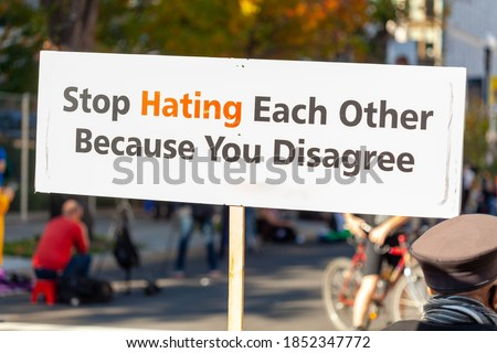 A message written on a banner placed in the street says: ' Stop Hating Each Other Because You Disagree ' . A peaceful slogan for tolerance to differing ideas and political views supporting harmony. Stock photo ©