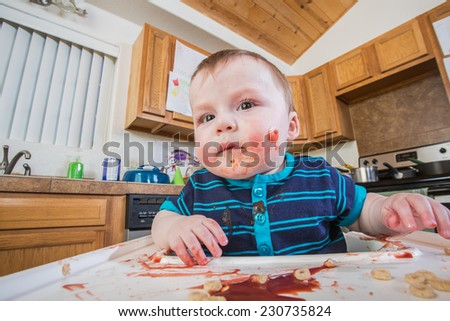 A messy child eats breakfast in the kitchen