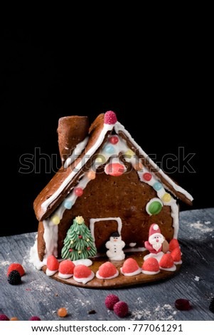 a messy homemade gingerbread house on a rustic wooden table, againt a black background with a blank space on top