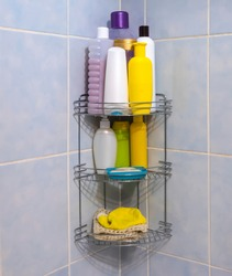 A metal bathroom grate shelf filled with body and hair care products weighs on a blue tile in the corner.