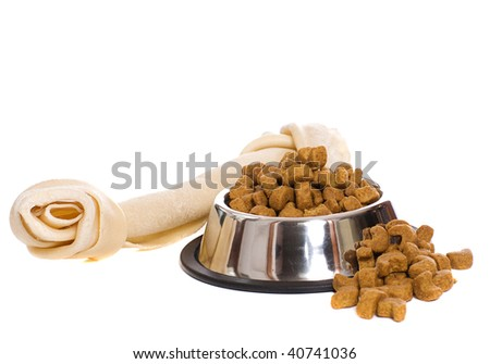 A metal bowl filled with dry dog food along with a large rawhide bone, isolated against a white background