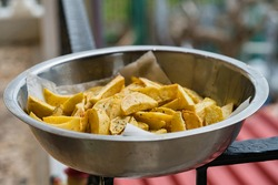 A metal bowl full of freshly fried delicious potatoes. Ready to eat in the countryside. Bon appetite!