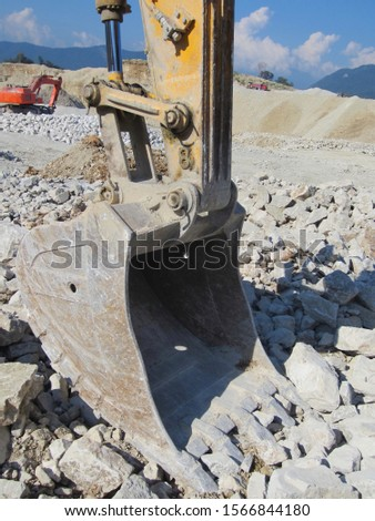 A metal bucket of a excavator digs a stone surface in a mining quarry. Road machinery for digging and digging the earth and other surfaces against the blue sky. #1566844180