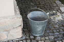 A metal bucket on the ground in front of a building in the street