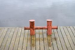 A metal dock for pleasure boats on wooden pedestrian bridge in the bay.