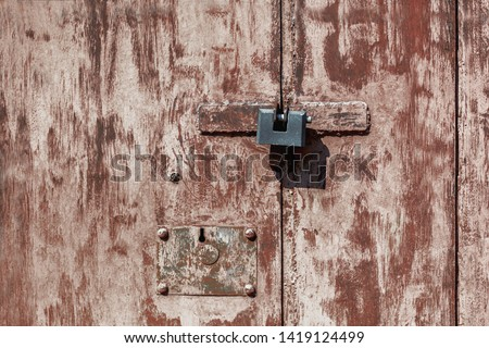 A metal door of a warehouse unevenly painted with a brush, closed on a padlock and a dead lock. No access. #1419124499