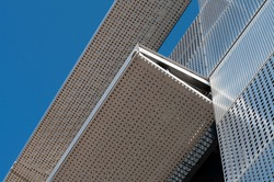a metal facade of an office building covered with perforated steel sheets on a sunny day