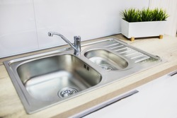 A metal faucet with a sink in the new kitchen.