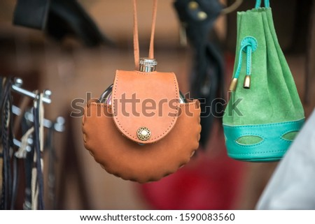 A metal flask in a handmade brown leather case hangs at the fair. The concept of travel and manual creativity.