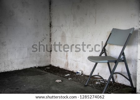 A metal folding chair in a dirty room. Concept of loneliness, depress, alone, nobody, homeless and facing problem.