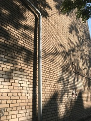 A metal galvanized tube for the drain of a rain head from the roof of the house runs down against the brick wall of an apartment building