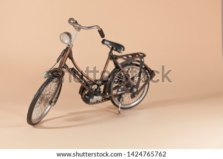 A metal motorized bike is standing on a pink surface #1424765762