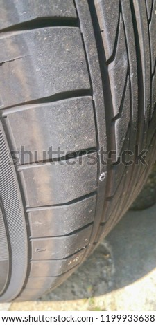 A metal nail stuck in the tyre wheel of a vehicle.  #1199933638