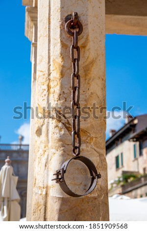 A metal neck iron on a pillory made of stone, which hangs down from a chain and where in former times prisoners were chained, who were put on the pillory Stockfoto ©