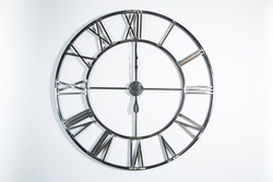 A metal openwork clock with Roman numerals, clock face, dial on a white wall, isolated on a white background. Six o'clock on a elegant wall clock.