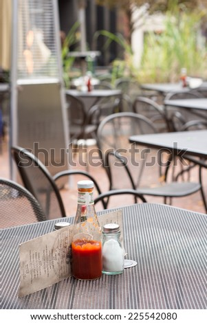 A metal outdoor restaurant table with a ketchup bottle, salt shaker, and menu. An outdoor heater and other tables are in the background.