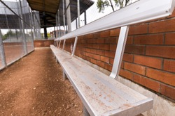A metal players bench with a dirt floor behind a fence in a baseball dugout.