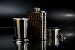 A metal pocket flask for alcoholic beverages with a folding metal cup, shot against a dark background.