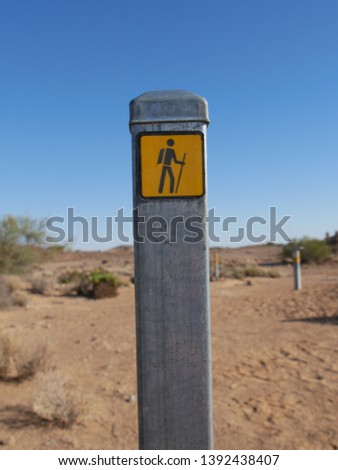 A metal pole with a hiking marker in the desert near Mound Springs on the Oodnadatta Track with desert plants, sand & other poles marking the trail on soft focus on the background South Australia