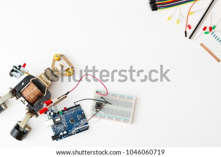 A metal robot and an electronic board that can be programmed. Robotics and electronics. Lab in the school. Mathematics, engineering, science, technology, computer code. STEM education for kid.