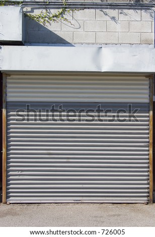 A metal rollup door protects a garage. - stock photo