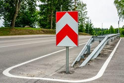 a metal safety barrier with a red and white striped traffic sign