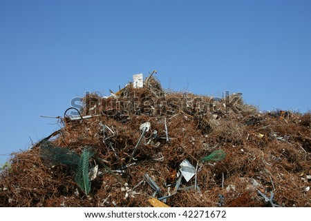 a metal scrap heap with different kinds of metal photographed in the summer sun at a commercial recycling center with blue sky in the background