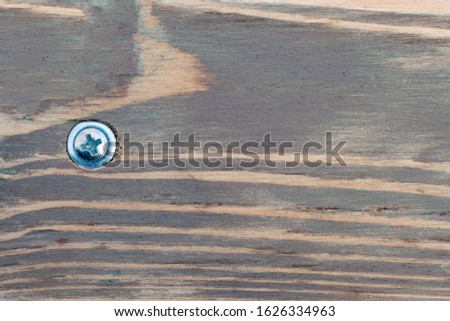 A metal screw with a cap is screwed into a decorative wooden shield