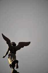 A metal sculpture of a running angel in front of a church in Mexico.