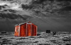 a metal shed rusts away on the shingle beach at dungeness, south east england. A black and white image with a colour pop on the corroded shack itself.