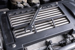 A  metal spanner  under the hood of the car on an oil cooler. Concept of car repair and tools in car service