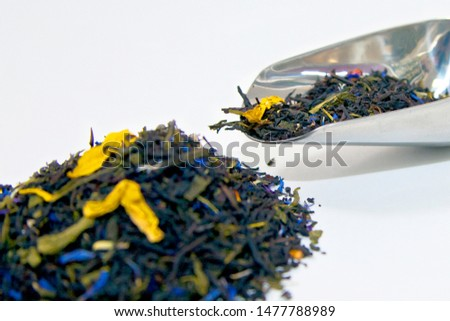 a metal spoon with dry tea leaves lies next to a bunch of tea leaves. tea leaves out of focus.