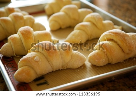 A metal tray of fresh baked holiday rolls for a Thanksgiving type setting