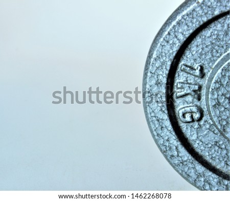 A metal weight against a plain background with the words 1 kg imprinted on the side