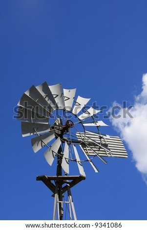 A metal wind pump or mill against a blue sky.